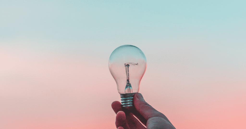hand holding a lightbulb for post ideas for social media in june cover image